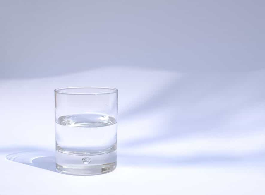 Photo of a glass tumbler of water half full